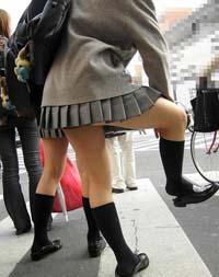 グレーのスカートにグレーのカーディガン、膝を上げソックス直してます。革靴のかかとを踏んづけていて、だらしなく見えてしまうJKです。