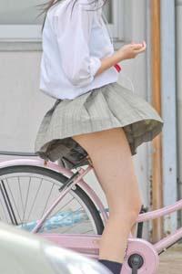 自転車にまたがるJK。風でスカートがフワリとパンツが見えそうです。